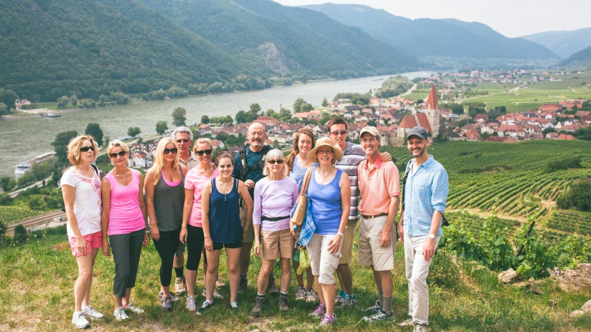 group of people in Austria by river and vineyards.