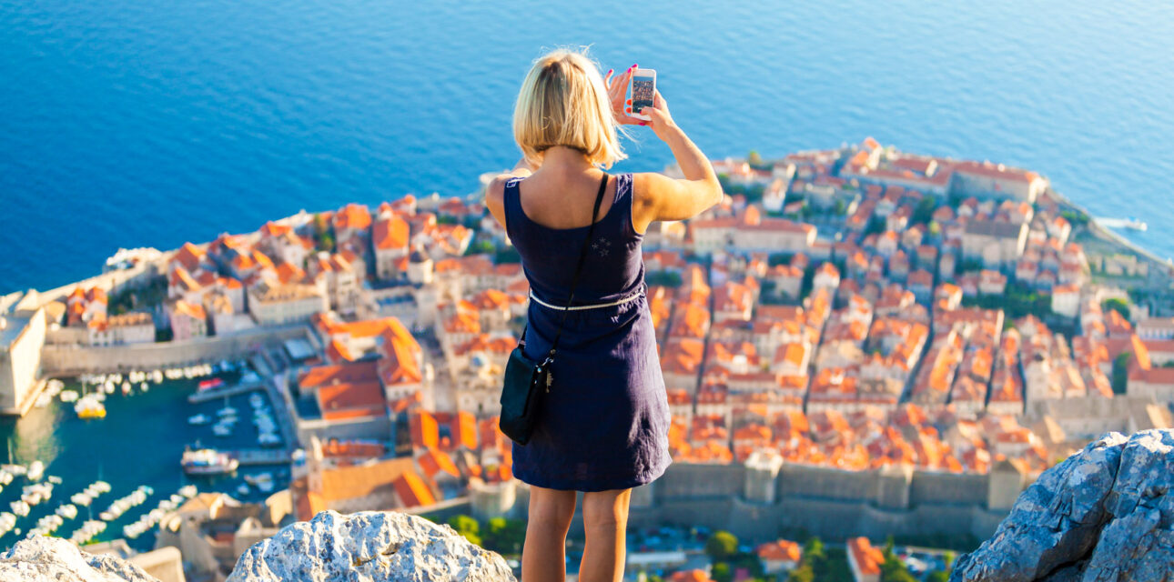 A girl taking a picture of a city landscape in croatia.