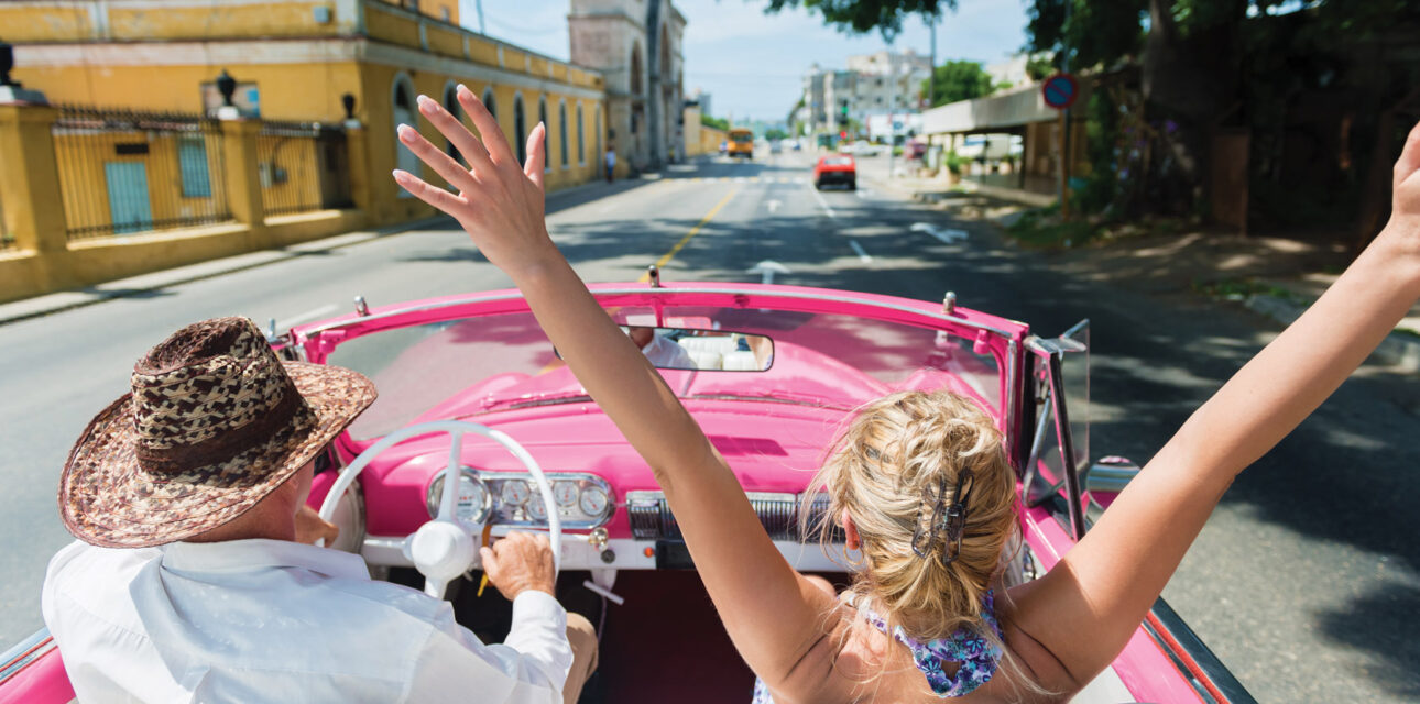 People driving in a convertible in Cuba.