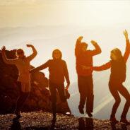 Young people dancing at sunset.