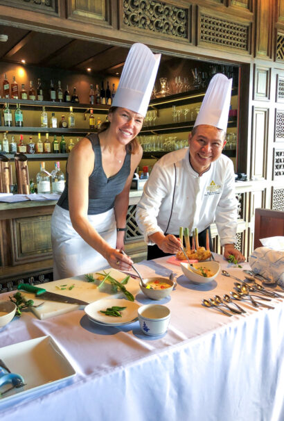 A woman learning from a chef.