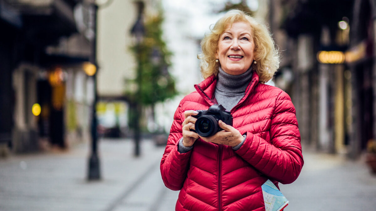 An elder woman taking a picture of where she's traveling.