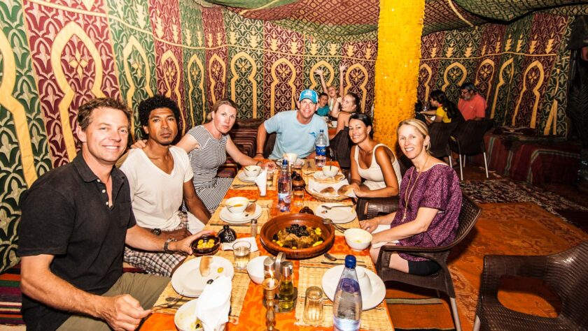A group of adults eating dinner around a table.