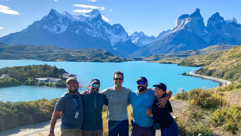 A group shot of tour guides with a mountain landscape backdrop.