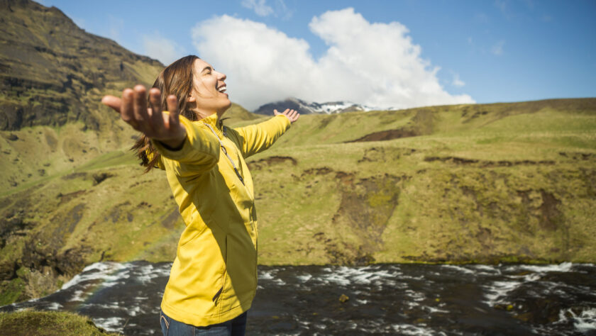 A woman smiling with her arms outstretched.