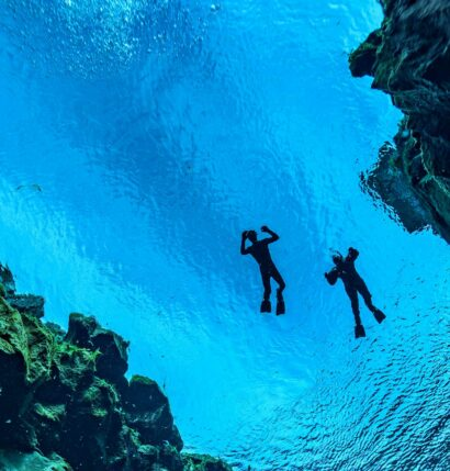 An underwater view of two people swimming in Iceland.