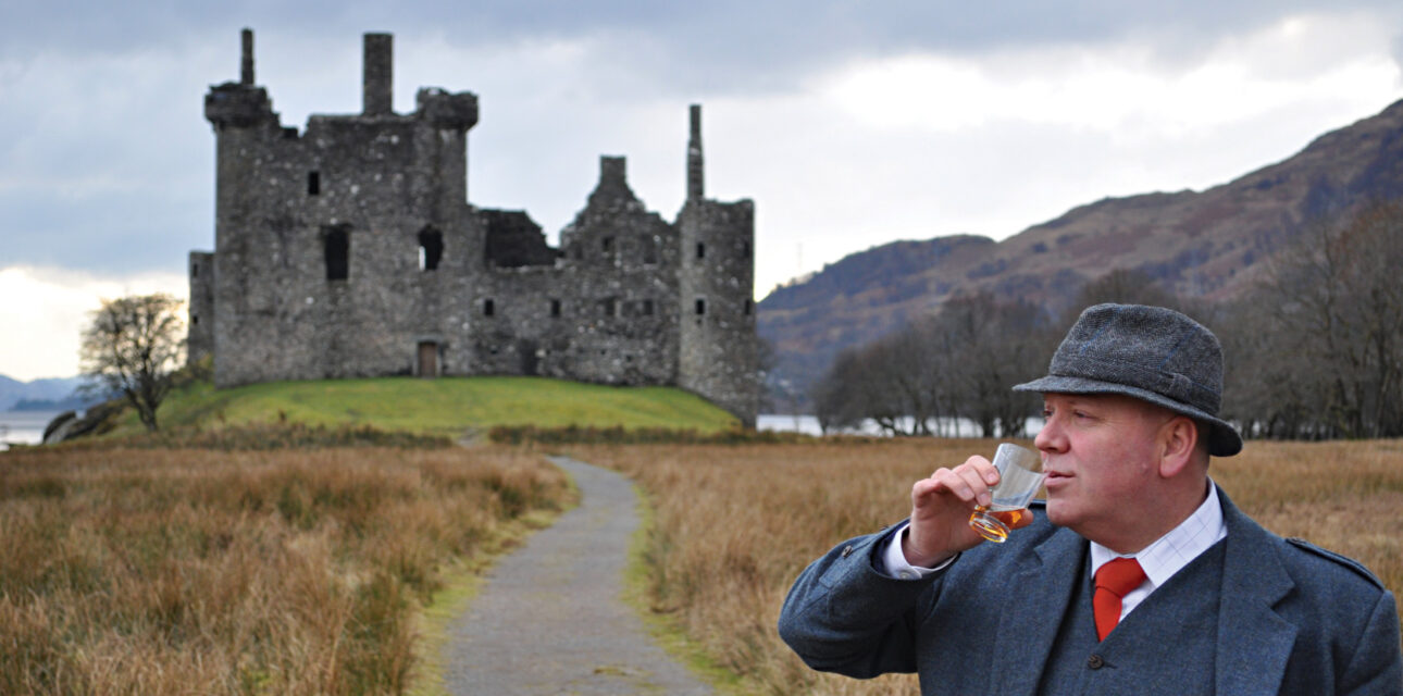 A man drinking next to a castle in the UK.