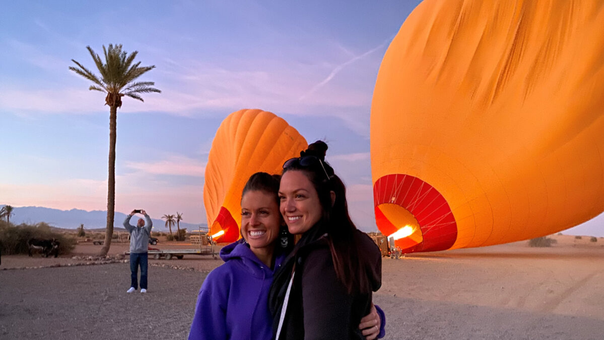 Two woman posing in front of a hot air balloon.