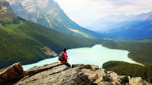 A young person sitting on a cliff looking out at a body of water.