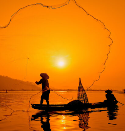 A silhouette of two people on a boat with a fishing net.