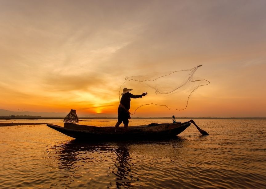 Asia Cambodia Mekong river sunrise fisherman casting net into river water