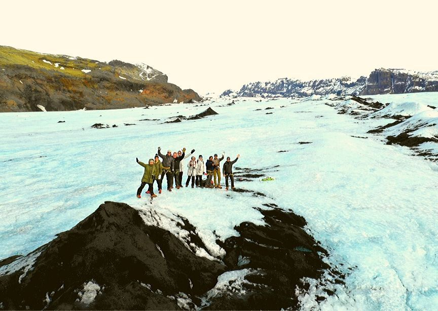 Iceland group winter tour waving from glacier hike