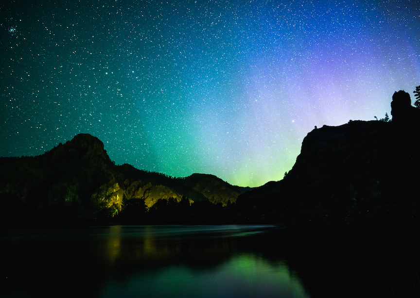 Montana mountains and lakes with northern lights in starry skies