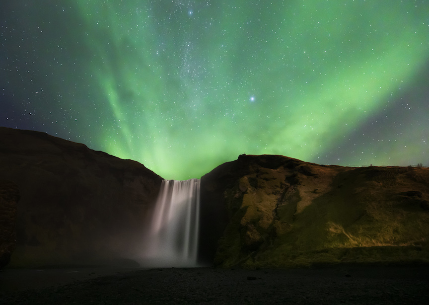 Iceland waterfall at night with the northern lights and stars green glow
